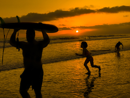 Venice Beach CA - Surfer carries board, boy dances as the sun sinks into the ocean at sunset